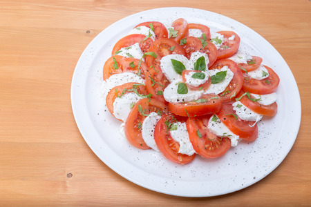 Tomato, mozzarella cheese and basil leaves salad in a white circular dish on a natural oak wood brown table - top view Stock Photo