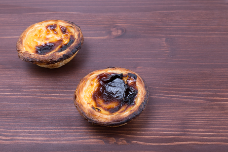 Two delicious egg tart pastry - Pastel de Nata from Portugal on a natural ipe wood board
