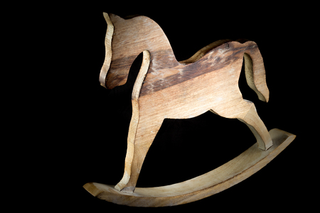 sculpted: Rocking Horse carved on natural wood isolated on black background Stock Photo
