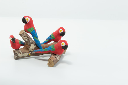 Macaws made in clay seated on a wood branch isolated in white background