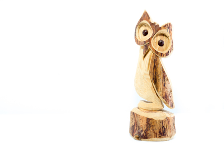 Owl sculpted on natural wood trunk isolated on white background