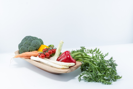 Super fresh vegetables in a handmade natural real wood bowl - cherry tomatoes, carrots with greens top, bell pepper, broccoli, white asparagus with white background Stock Photo
