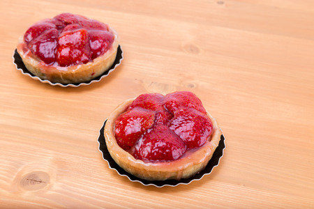 recipe decorated: Strawberry tartellete tart pie on an oak natural wood table