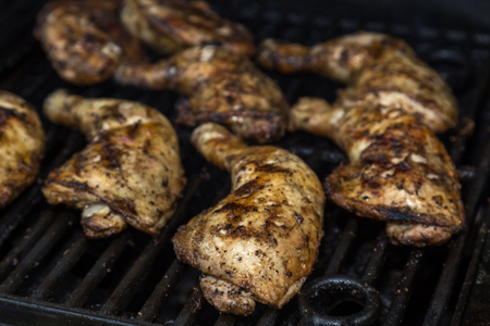 Chicken leg quarter thighs on a barbecue grill, golden and juicy -  front view Banco de Imagens