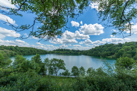 shinning: Great green water german lake in a vulcan  with amazing clouds in a sun shinning day - Maar lakes from inside of the wood forest Stock Photo
