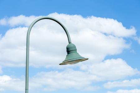 Hanging street lamp on blue sky background with clouds
