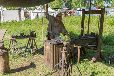 medieval blacksmith: Useldange, Luxembourg, July 6, 2017- Medieval Fair Festival. A medieval blacksmith working on fire during a medieval reenactment festival.