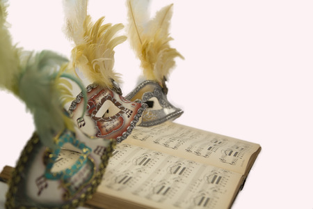 Three colorful carnival venetian mask with feathers on an open musical book. photo