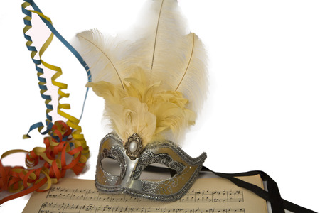 Silver carnival venetian mask with feathers and colorful serpentine on music page. photo