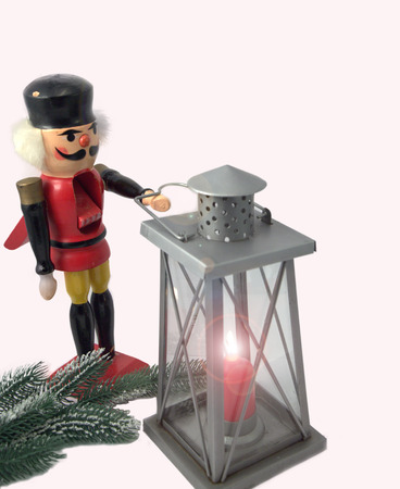lit lamp: The wooden nutcracker with the lit lamp and a fir-tree branch.