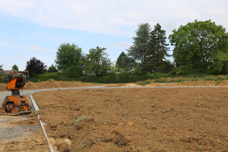 Earth rammer, prepared soil and built road for the construction of a new residential settlement in Germany.