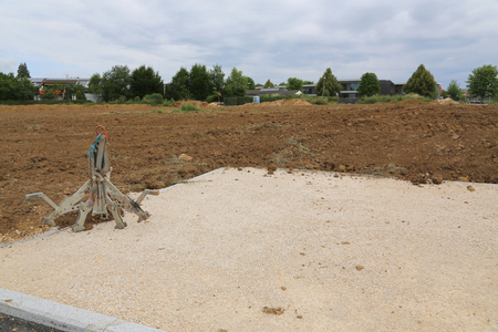 Excavator gripper, prepared soil and built road for the construction of a new residential settlement in Germany.