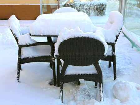 Table and chairs of outdoor cafe covered with snow in a winter day