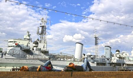 London, Great Britain -May 23, 2016:  Tired tourists rest near the museum HMS Belfast, World War II museum with 9 decks and naval weapons, permanent mooring on the Thames.