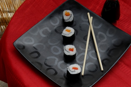 Four sushi rolls placed diagonally on a black plate photo