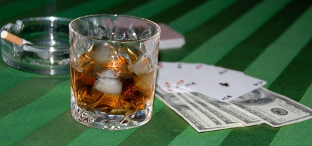 Play cards, ashtray, money and glass of whiskey on a green tablecloth photo