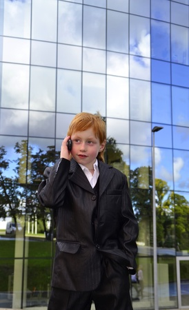 Smart boy talking by phone in front of an office building photo