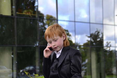 Smart boy talking by phone in front of an office building Stock Photo - 10563876