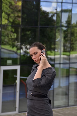 Strict woman talking by phone in front of an office building Stock Photo - 10575893
