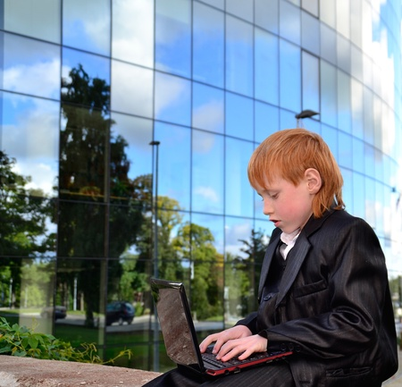 Smart boy working with laptop in front of an office building photo