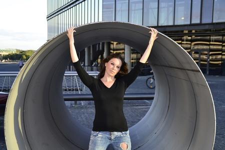 Girl standing inside the metallic pipe photo