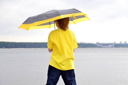 t off: Red head boy showing his back standing under yellow umbrella on a seashore