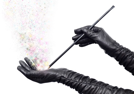 Fairy hands in long black gloves holding magic wand and casting spell