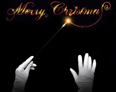 Wizard handen tekenen 'Merry Christmas' op een zwarte achtergrond