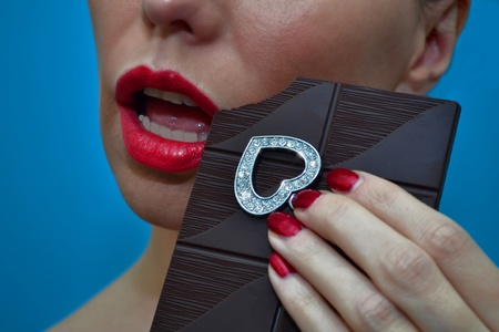 Dangerous woman intending to eat diamond heart with dark chocolate bar Stock Photo - 11216881