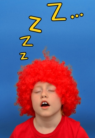 opened mouth: Funny boy in red curly wig making sleepy face