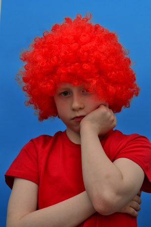 malcontent: Funny boy in red curly wig makes unpleased face