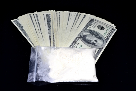 wrongful: Bag with white powder put on a bundle of dollars Stock Photo