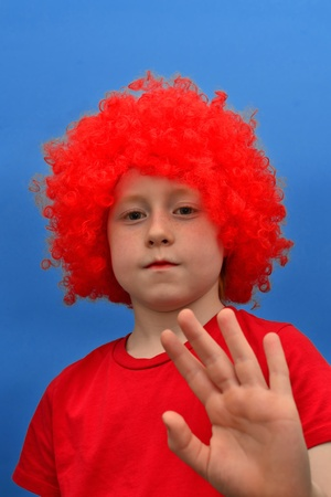 contradict: Funny boy in red curly wig demonstrating his objection Stock Photo