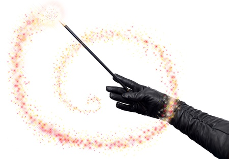Magician hands in long black gloves holding magic wand and casting spell