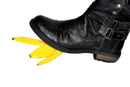 Black boot stepping on a banana peel photo