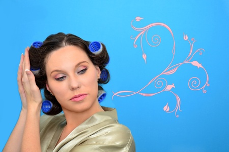 Pretty woman with beautiful pink ornament correcting curlers on her head photo