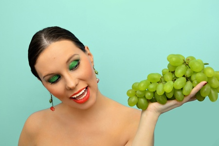 Pretty woman intending to eat bunch of grapes Stock Photo - 12076867