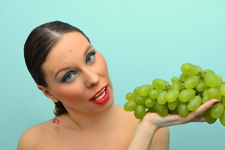Pretty woman intending to eat bunch of grapes Stock Photo - 12466788