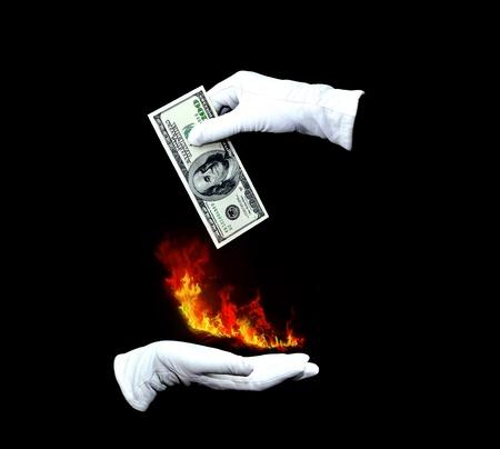 Mago manos con guantes blancos que los dólares y el fuego