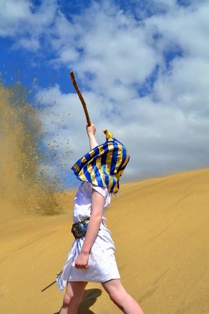 Powerful boy pharaoph calling sand storm in a desert photo