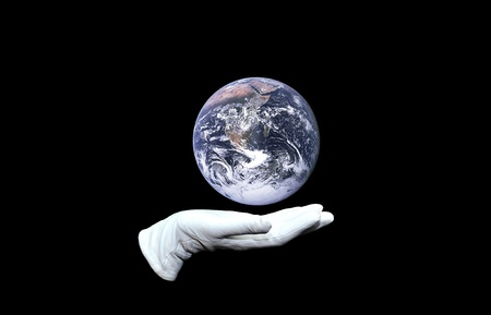 Mano en guante blanco sosteniendo el globo del mundo