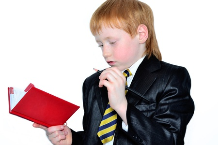 Office boy making notes in his diary photo