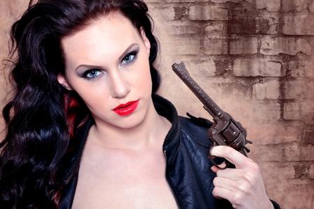 Retrato de una mujer joven que sostiene la pistola photo