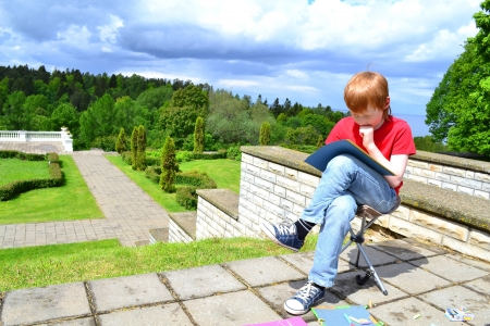 Boy painting in a beautiful park with looming storm clouds photo