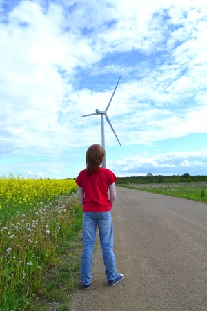 Boy in a red tshirt and jeans  staring at a windmill photo