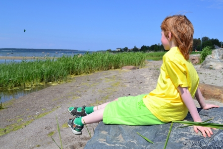 Boy sitting on a big boulder near the sea photo