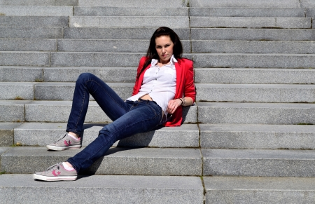 red jeans: Young girl in red jacket relaxing on a stairway Stock Photo