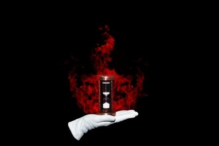 Illusionist houdt het branden van een zandloper symboliseert brandtijd