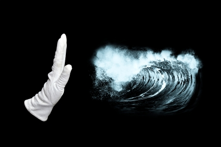 Hand in white glove stopping huge wave photo