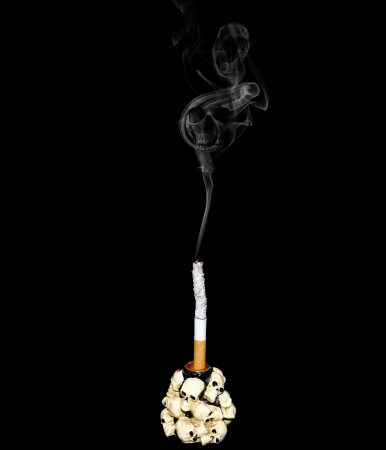 White cigarette in a candlestick decorated with human skulls photo